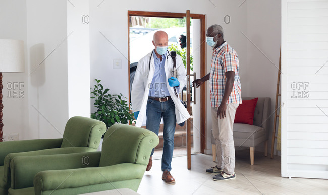 Senior African American man greeting caucasian senior doctor both wearing masks at home. healthcare hygiene protection during coronavirus covid 19 pandemic.