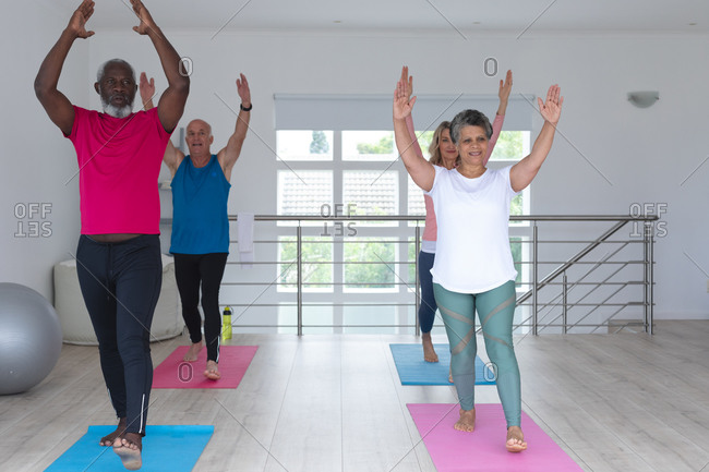 Diverse group of seniors taking part in fitness class at home. health fitness wellbeing at senior care home.