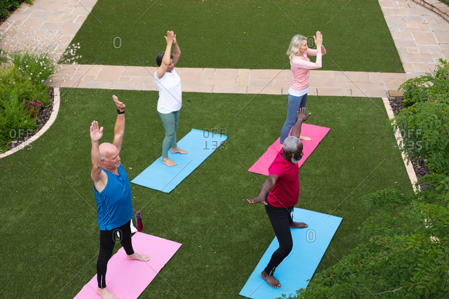 Diverse group of seniors taking part in fitness class in garden. health fitness wellbeing at senior care home.