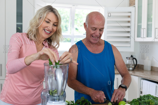 Senior caucasian man and woman preparing fruit and vegetable health drinks. health fitness wellbeing at senior care home.