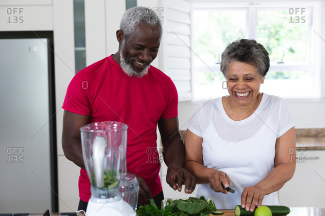 Senior African American man and woman preparing fruit and vegetable health drinks. health fitness wellbeing at senior care home.