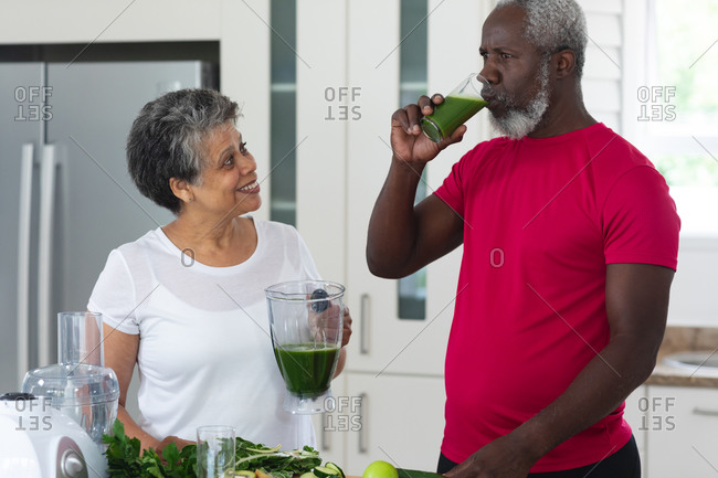 Senior African American man and woman droning fruit and vegetable health drinks. health fitness wellbeing at senior care home.