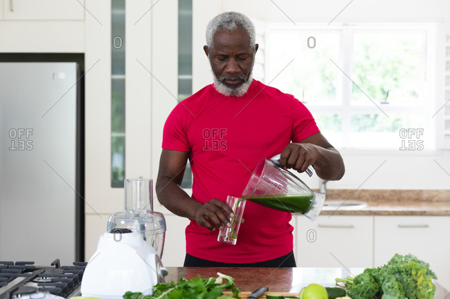 Senior African American man pouring fruit and vegetable health drink into a glass. health fitness wellbeing at senior care home.