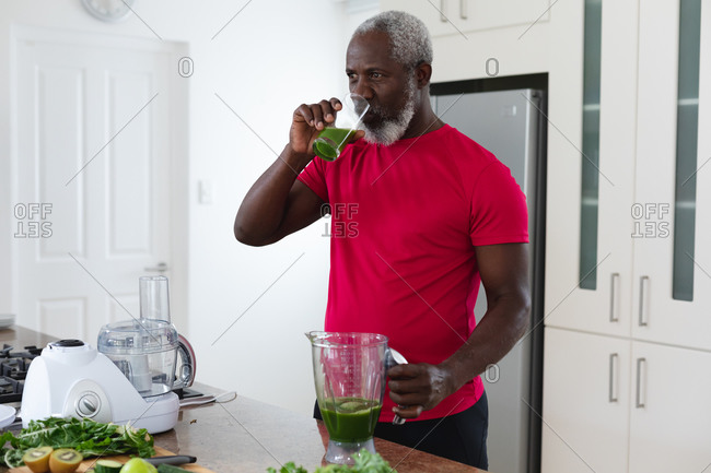 Senior African American man drinking fruit and vegetable health drink. health fitness wellbeing at senior care home.