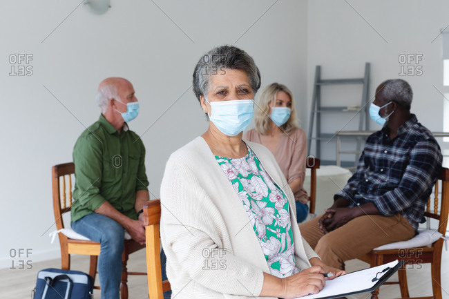 Diverse group of seniors wearing face masks talking during a group therapy session at home. health hygiene wellbeing at senior care home during coronavirus covid 19 pandemic.