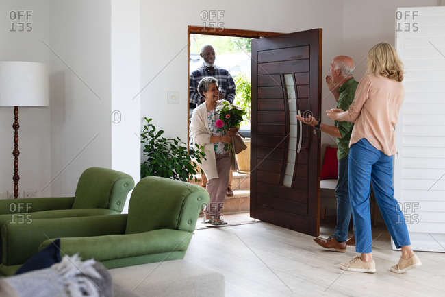 Senior caucasian couple greeting senior African American couple all wearing face masks at home. senior retirement lifestyle friends socializing.