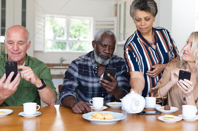 Senior caucasian and African American couples sitting by table drinking tea using smartphone at home. senior retirement lifestyle friends socializing.