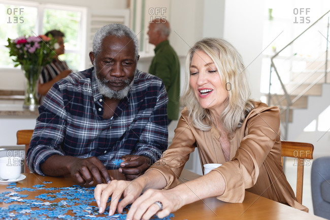 Senior caucasian woman and African American man sitting by table doing puzzles at home. senior retirement lifestyle friends socializing.