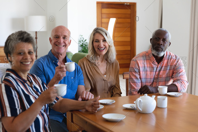 Senior caucasian and African American couples sitting by table drinking tea at home. all looking at the camera and smiling. senior retirement lifestyle friends socializing.