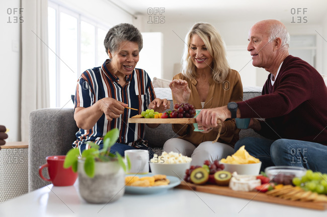 Senior caucasian and African American couples sitting by table eating cheese and fruits at home. senior retirement lifestyle friends socializing.