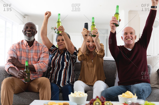 Senior caucasian and African American couples sitting on couch watching game drinking beer at home. senior retirement lifestyle friends socializing.