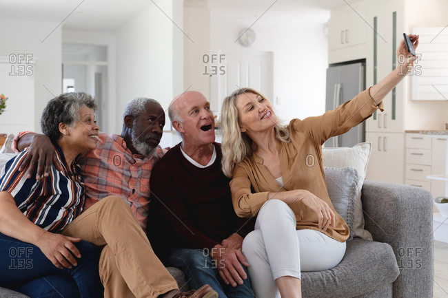 Senior caucasian and African American couples sitting on couch taking a selfie at home. senior retirement lifestyle friends socializing.