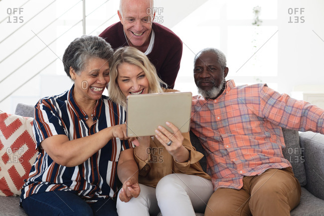 Senior caucasian and African American couples sitting on couch using digital tablet at home. senior retirement lifestyle friends socializing.