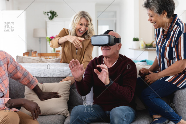 Senior caucasian and African American couples sitting on couch using vr headset at home. senior retirement lifestyle friends socializing.