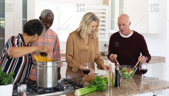 Senior caucasian and African American couples making pasta and salad at home. senior retirement lifestyle friends socializing.