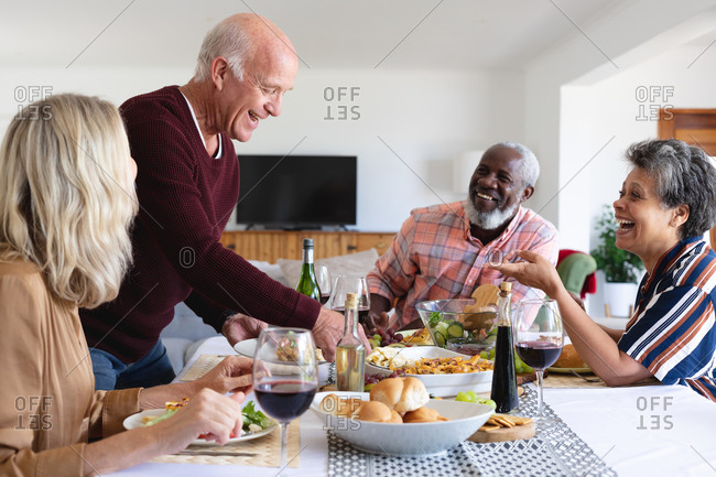 Senior caucasian and African American couples sitting by table eating dinner at home. senior retirement lifestyle friends socializing.