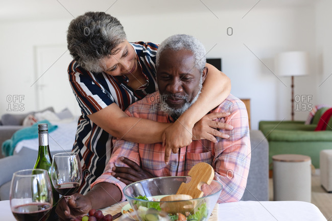 Senior African American couple sitting by table eating dinner and hugging at home. senior retirement lifestyle friends socializing.