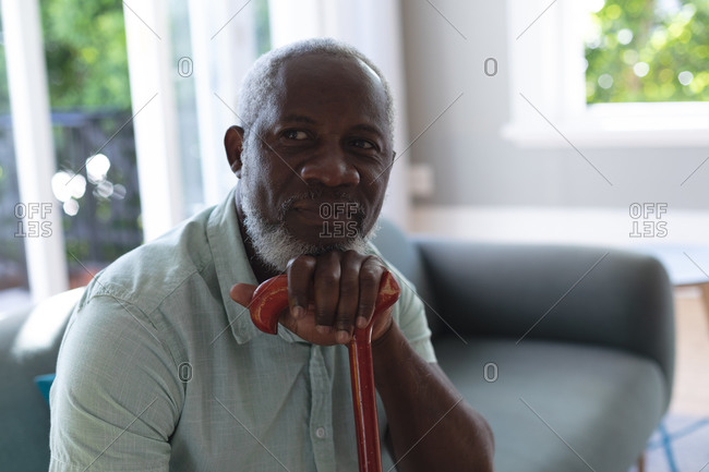 Portrait of senior African American man sitting in living room leaning on walking stick. staying at home in self isolation during quarantine lockdown.