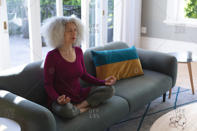 Senior caucasian woman sitting on couch in living room meditating. staying at home in self isolation during quarantine lockdown.