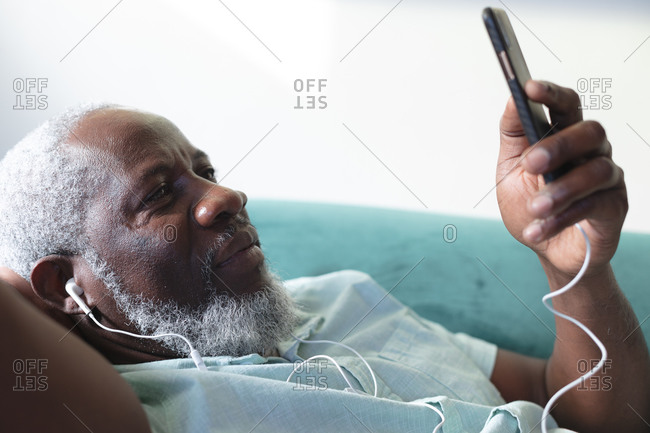 Senior African American man lying on couch using smartphone listening to music on earphones. staying at home in self isolation during quarantine lockdown.
