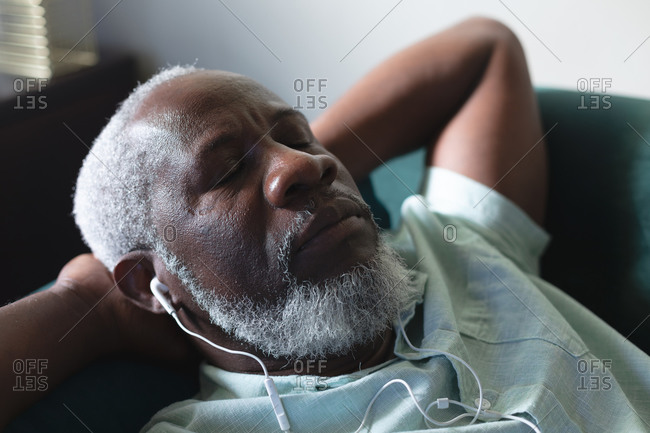 Senior African American man lying on couch sleeping listening to music on earphones. staying at home in self isolation during quarantine lockdown.