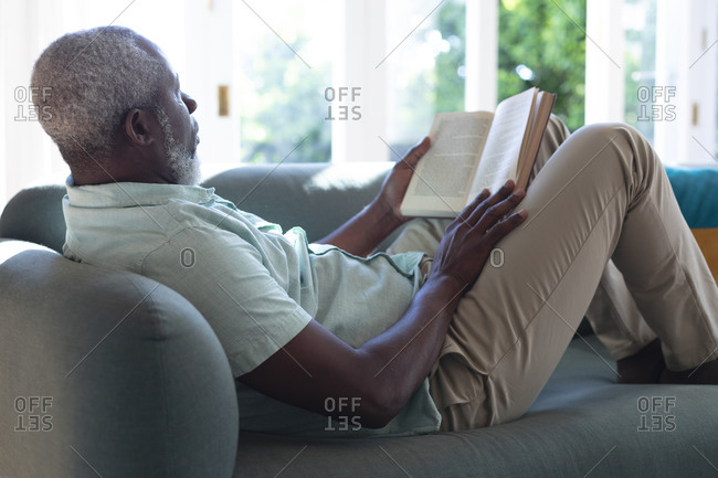 Senior African American man lying on couch reading book. staying at home in self isolation during quarantine lockdown.