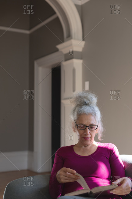 Senior caucasian woman sitting on couch in living room reading book. staying at home in self isolation during quarantine lockdown.