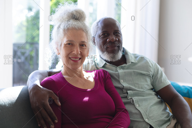 Senior mixed race couple embracing looking at the camera and smiling in living room. staying at home in self isolation during quarantine lockdown.