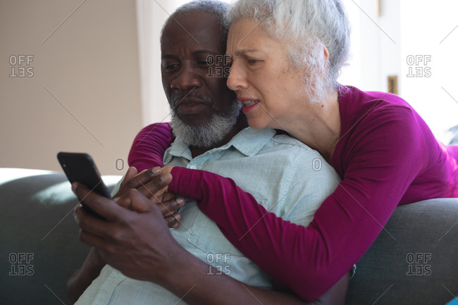 Senior mixed race couple embracing looking at smartphone together in living room. staying at home in self isolation during quarantine lockdown.