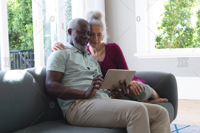 Senior mixed race couple sitting on couch looking at digital tablet together in living room. staying at home in self isolation during quarantine lockdown.