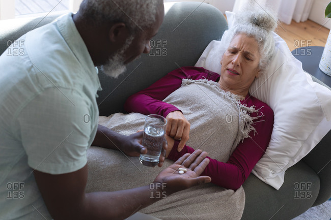 Senior caucasian woman lying sick on couch man passing medicine and water in living room. staying at home in self isolation during quarantine lockdown.