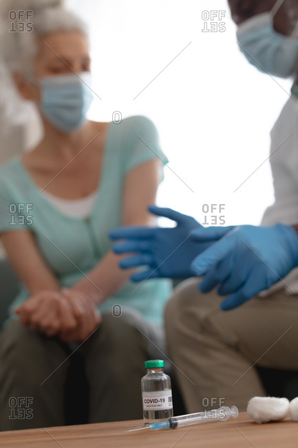 Senior African American male doctor preparing covid 19 vaccination for senior caucasian woman at home. healthcare and hygiene at home in self isolation during quarantine lockdown.