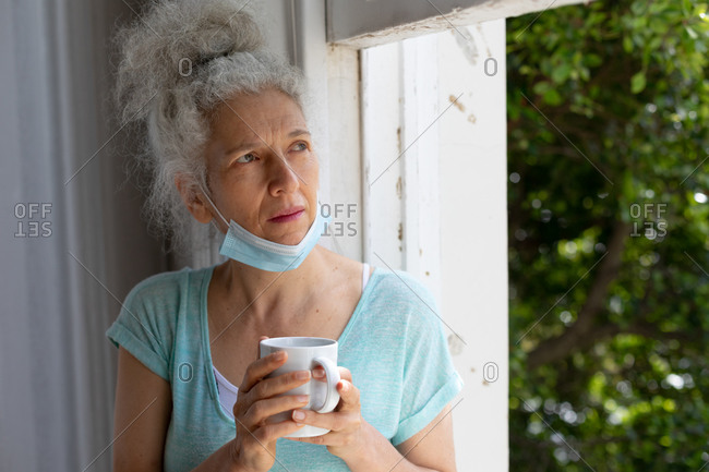 Senior caucasian woman standing by window drinking cup of coffee at home. staying at home in self isolation during quarantine lockdown.
