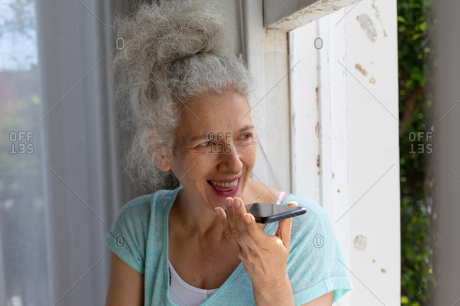 Senior caucasian woman standing by window talking on smartphone at home. staying at home in self isolation during quarantine lockdown.
