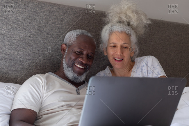 Senior mixed race couple in bedroom lying on bed using laptop. staying at home in self isolation during quarantine lockdown.