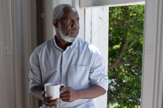 Senior African American man standing by window drinking coffee at home. staying at home in self isolation during quarantine lockdown.