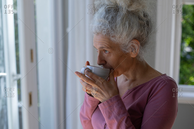 Senior caucasian woman standing by window drinking coffee at home. staying at home in self isolation during quarantine lockdown.