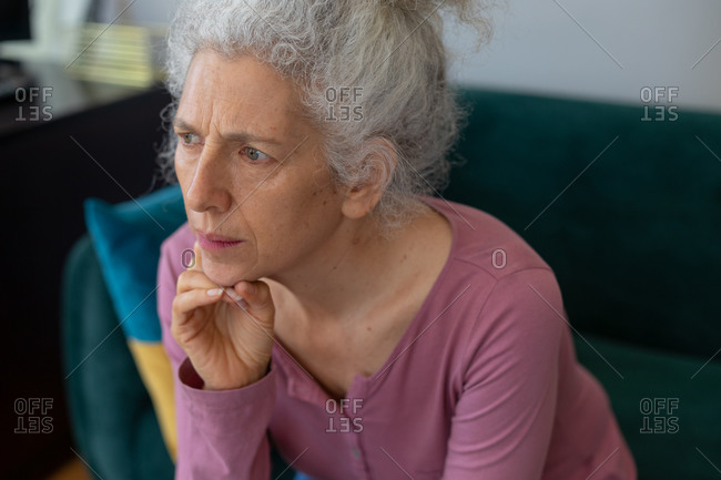 Senior caucasian woman sitting on couch rubbing her chin. staying at home in self isolation during quarantine lockdown.