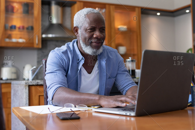 Senior African American man using laptop paying bills in dining room. staying at home in self isolation during quarantine lockdown.