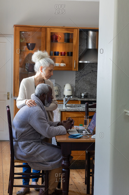 Senior mixed race couple using laptop paying bills together in dining room. staying at home in self isolation during quarantine lockdown.