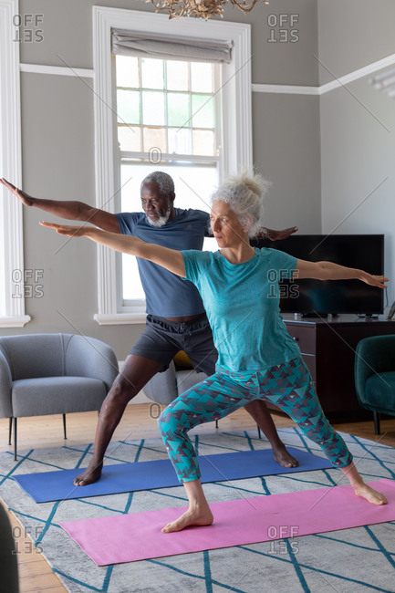 Senior mixed race couple wearing sports clothes exercising in living room. staying at home in self isolation during quarantine lockdown.