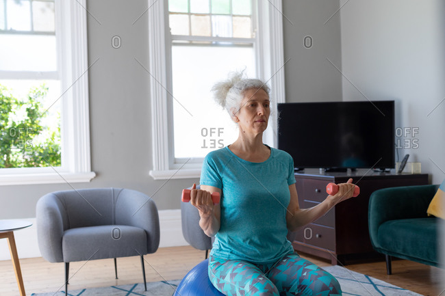 Senior caucasian woman wearing sports clothes exercising in living room. staying at home in self isolation during quarantine lockdown.