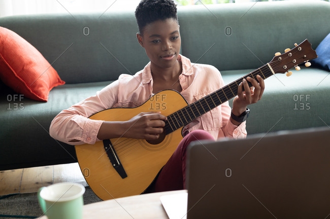 African American woman playing guitar while looking at the laptop at home. staying at home in self isolation in quarantine lockdown