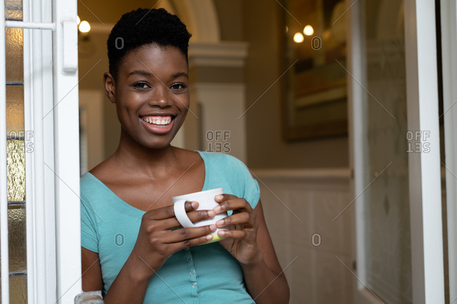 Portrait of African American woman holding coffee cup smiling at home. staying at home in self isolation in quarantine lockdown