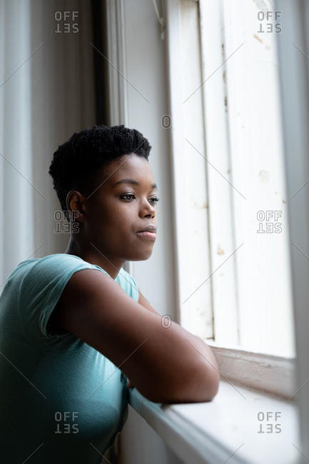 Portrait of African American woman looking out of the window at home. staying at home in self isolation in quarantine lockdown