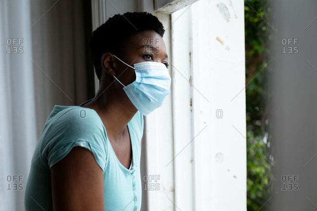 Portrait of African American woman wearing face mask looking out of the window at home. staying at home in self isolation in quarantine lockdown