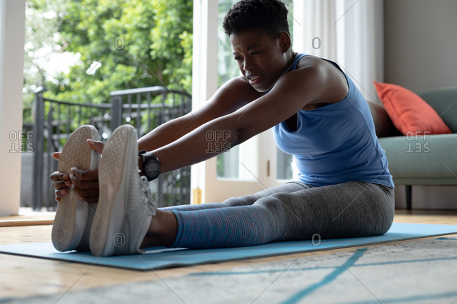 African American woman performing stretching exercise at home. staying at home in self isolation in quarantine lockdown