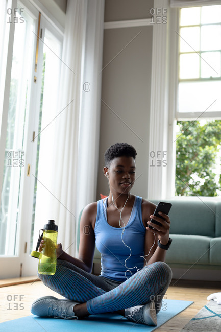 African American woman holding water bottle using smartphone at home. staying at home in self isolation in quarantine lockdown