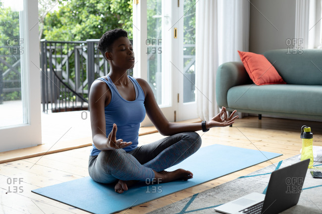 African American woman practicing yoga at home. staying at home in self isolation in quarantine lockdown