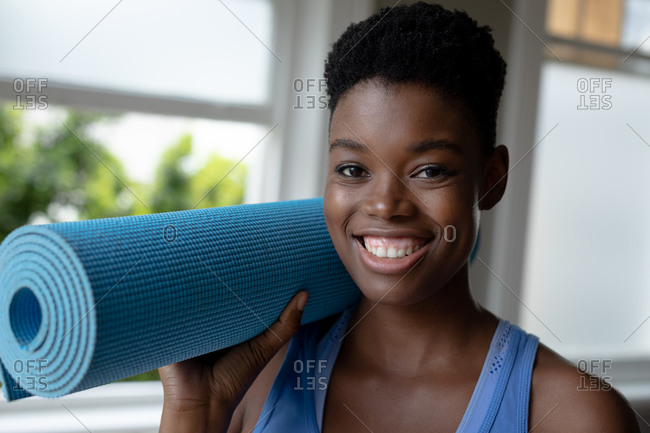 Portrait of African American woman smiling while holding yoga mat at home. staying at home in self isolation in quarantine lockdown